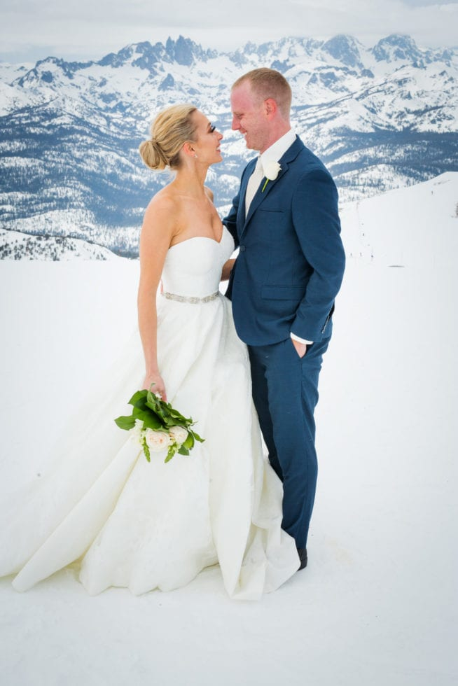 bride and groom standing on mammoth mountain and smiling at each other with snowy mountain in background