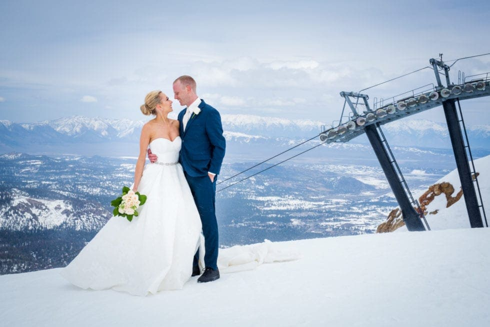 bride and groom looking at each other in front of ski lift in Mammoth Mountain with snow