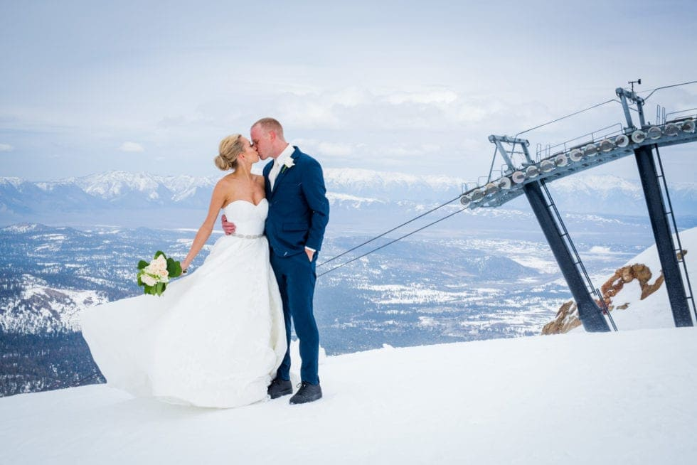 bride and groom kissing in front of ski lift in Mammoth Mountain with snow