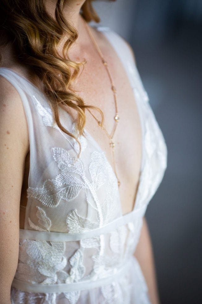 detail image of bride's dress and necklace
