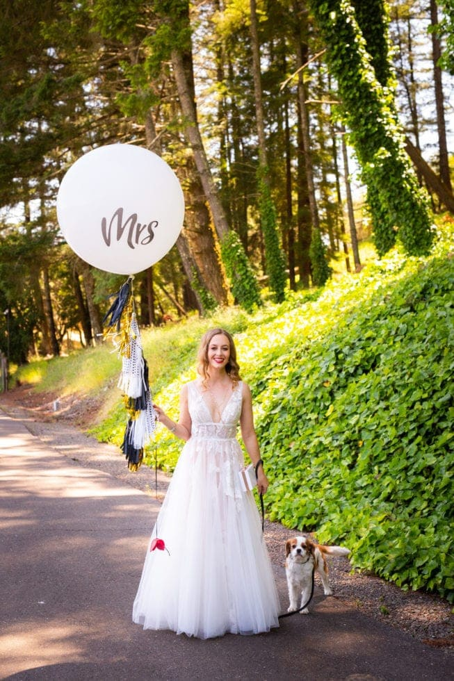 bride walking her dog and holding a balloon that says mrs in griffith woods