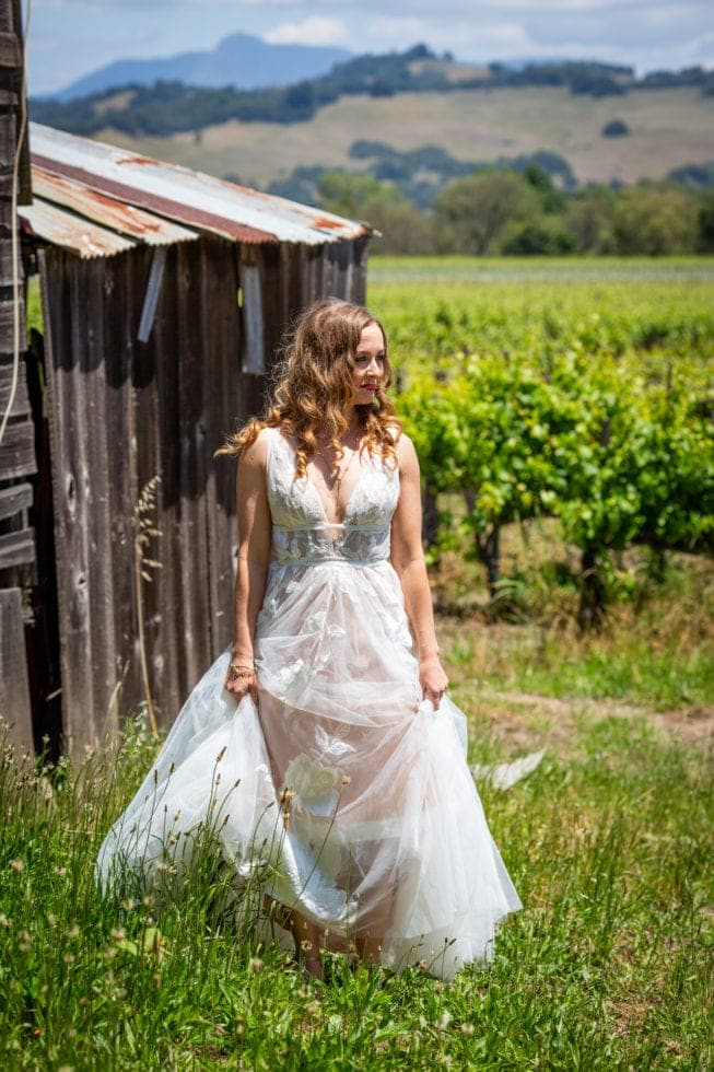 bride standing next to old barn in griffith woods