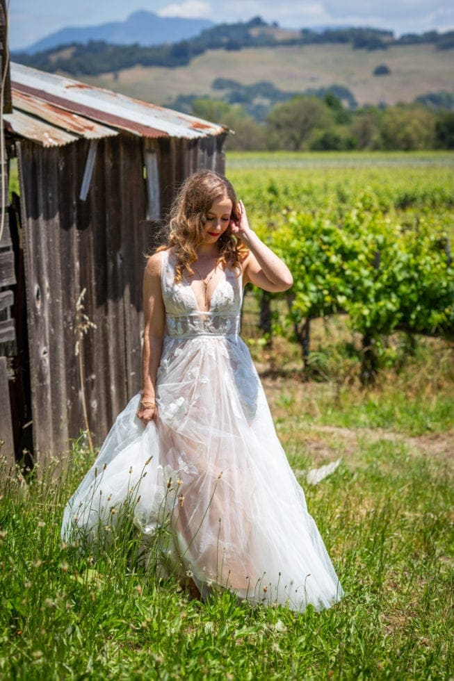 bride standing next to barn in griffith woods