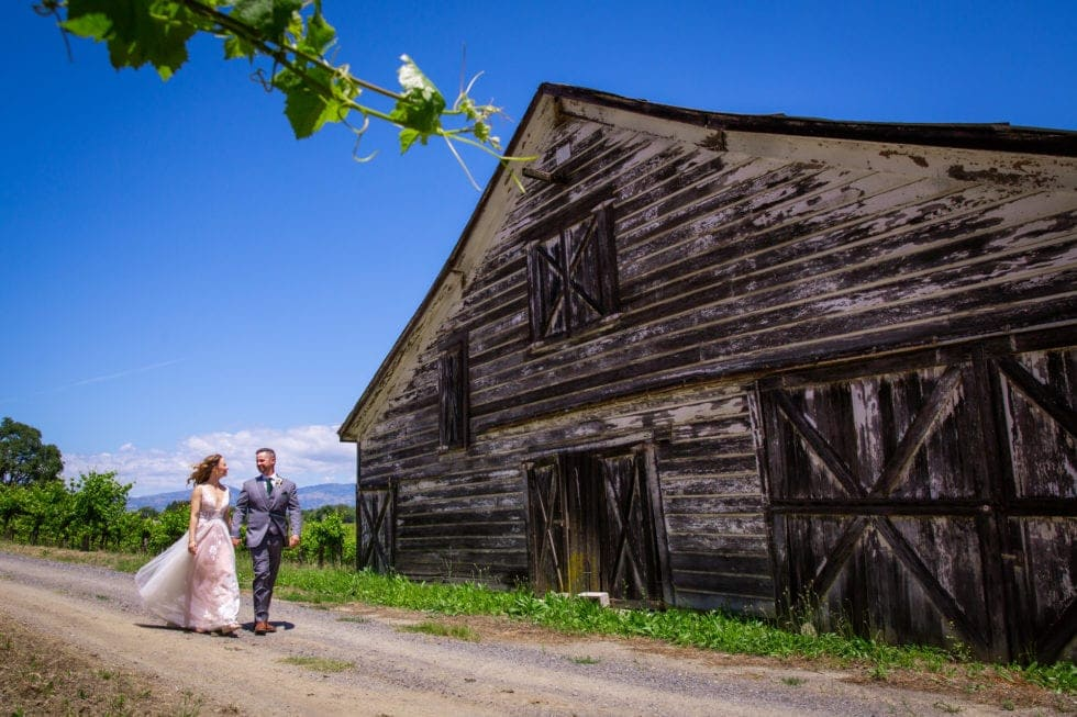 bride and groom walking on path next to old barn at griffith woods