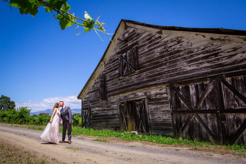 bride and groom kiss on path next to old barn at griffith woods