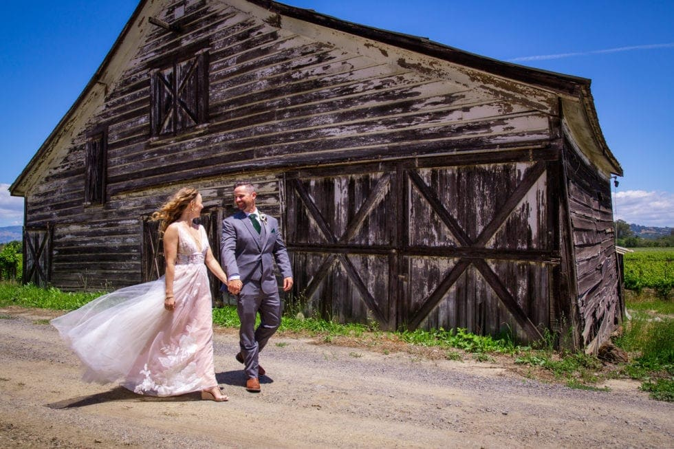 bride and groom holding hands and walking on a path next to an old barn at griffith woods