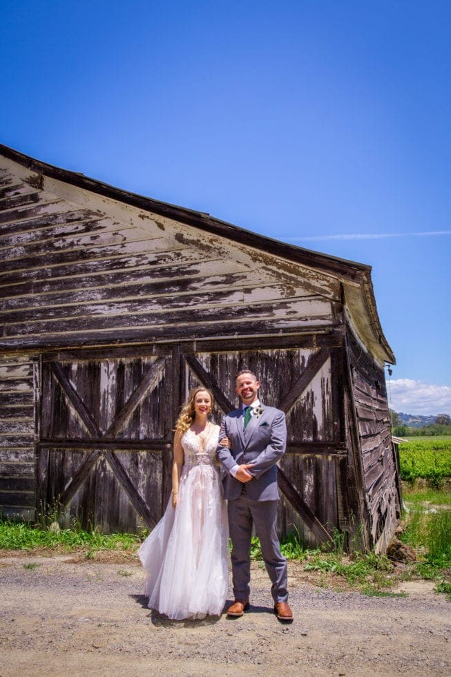 bride and groom standing in front of old barn at griffith woods