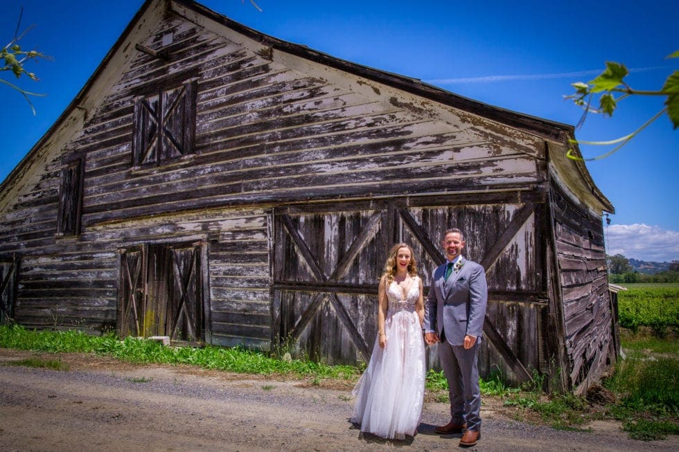 bride and groom smiling in front of old barn at griffith woods