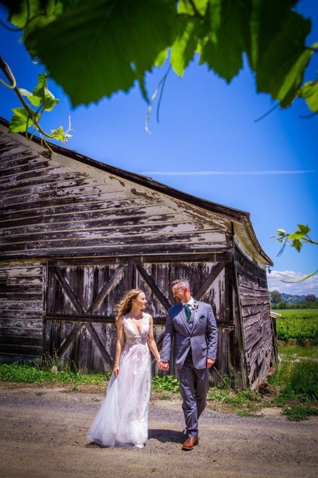 bride and groom looking at each other and standing in front of old barn at griffith woods