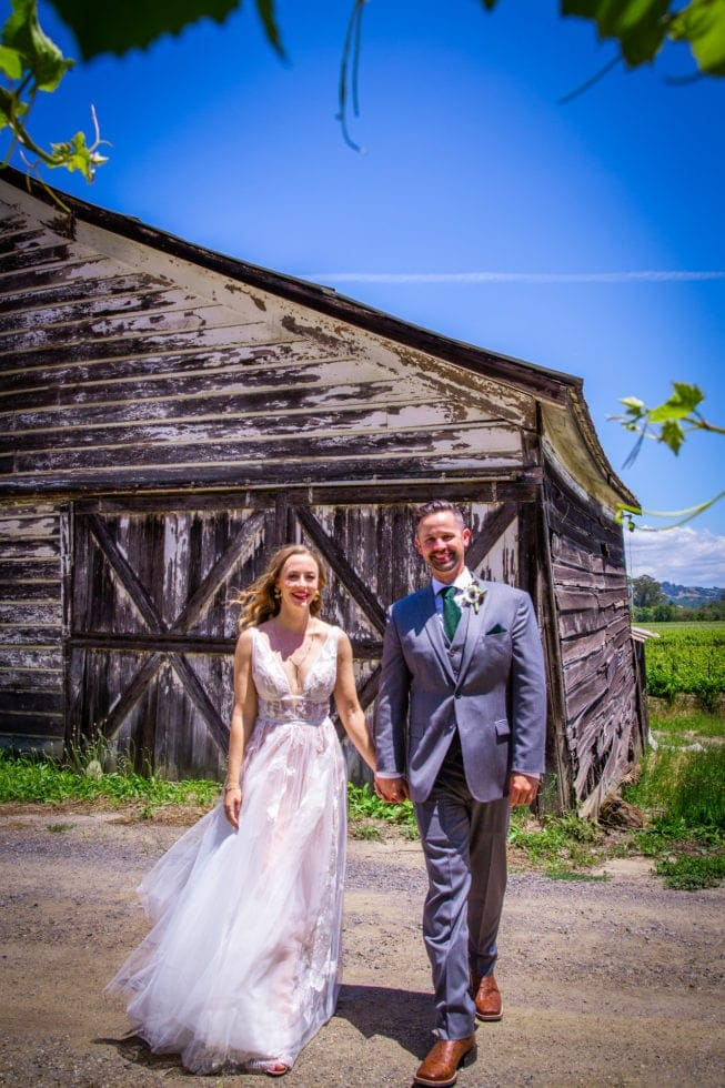 bride and groom smiling and walking toward camera in front of old barn at griffith woods
