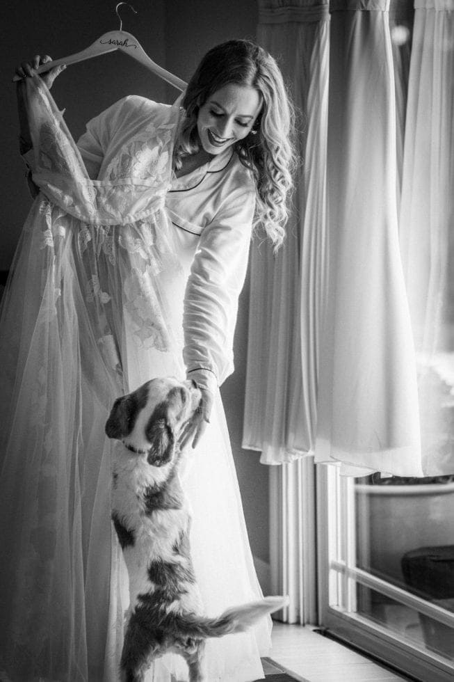 bride holds up wedding dress and pets her dog