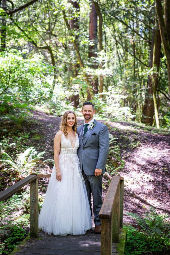 bride and groom smiling on bridge in griffith woods