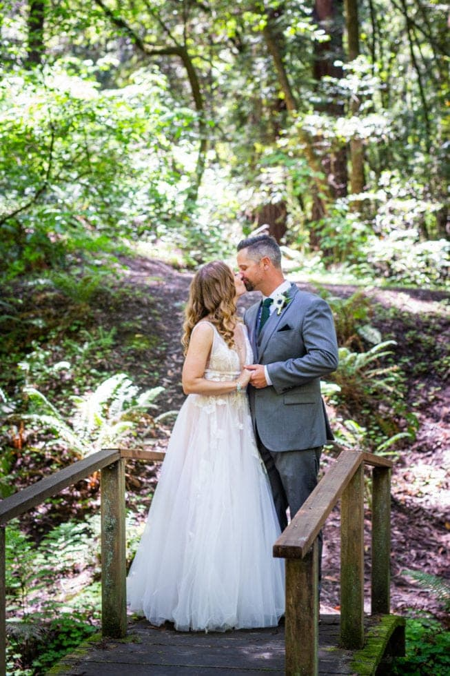 bride and groom kissing on bridge in griffith woods