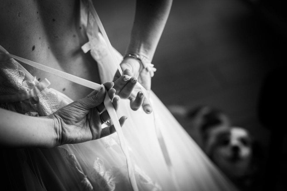 bride ties ribbon on the back of her wedding dress