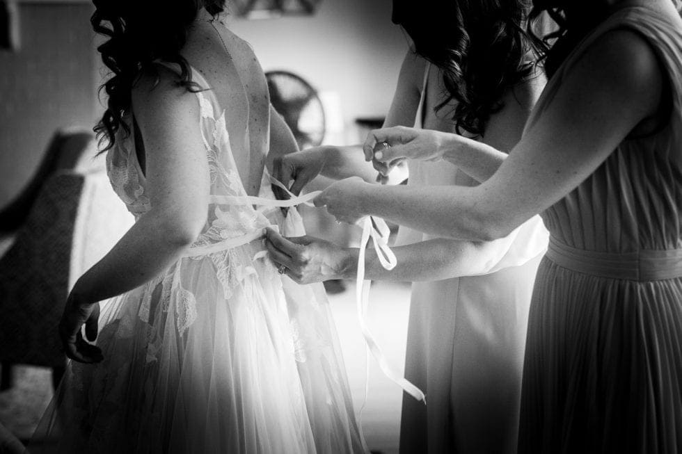 friends help bride tie ribbon on back of dress