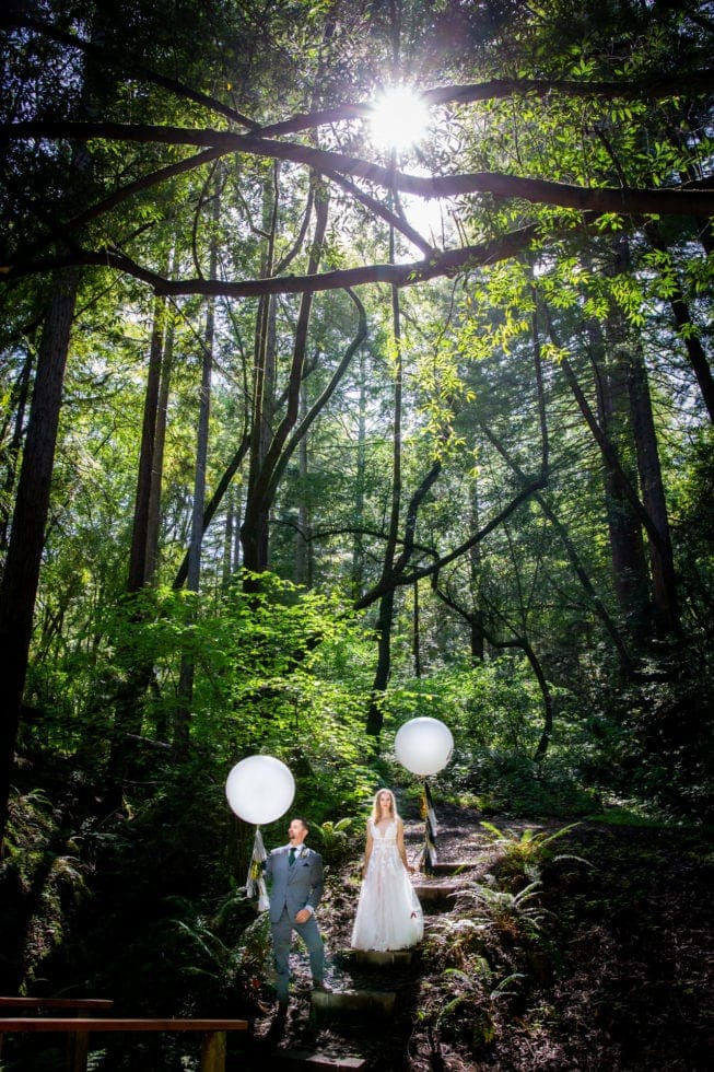 bride and groom holding balloons and standing on steps in griffith woods