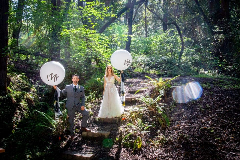 bride and groom holding mr and mrs balloons and standing on steps in griffith woods