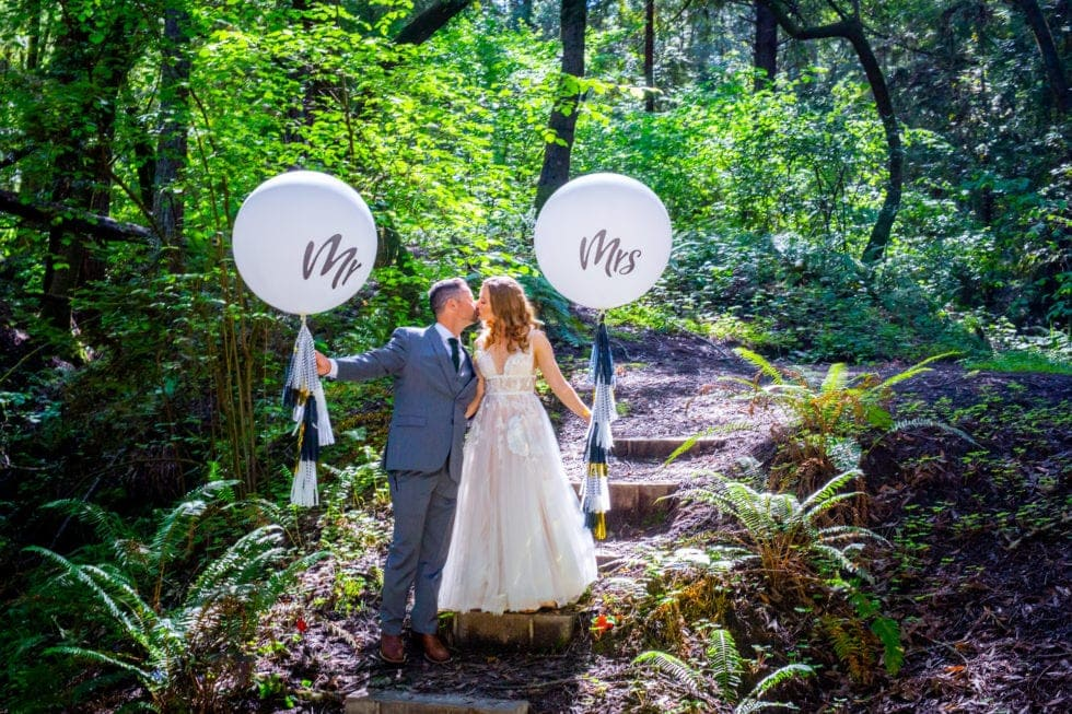 bride and groom holding balloons and kissing on steps in griffith woods