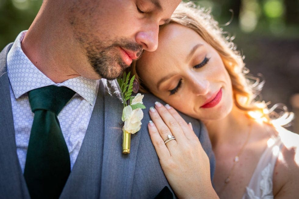 bride and groom lean on each other as bride shows off wedding ring