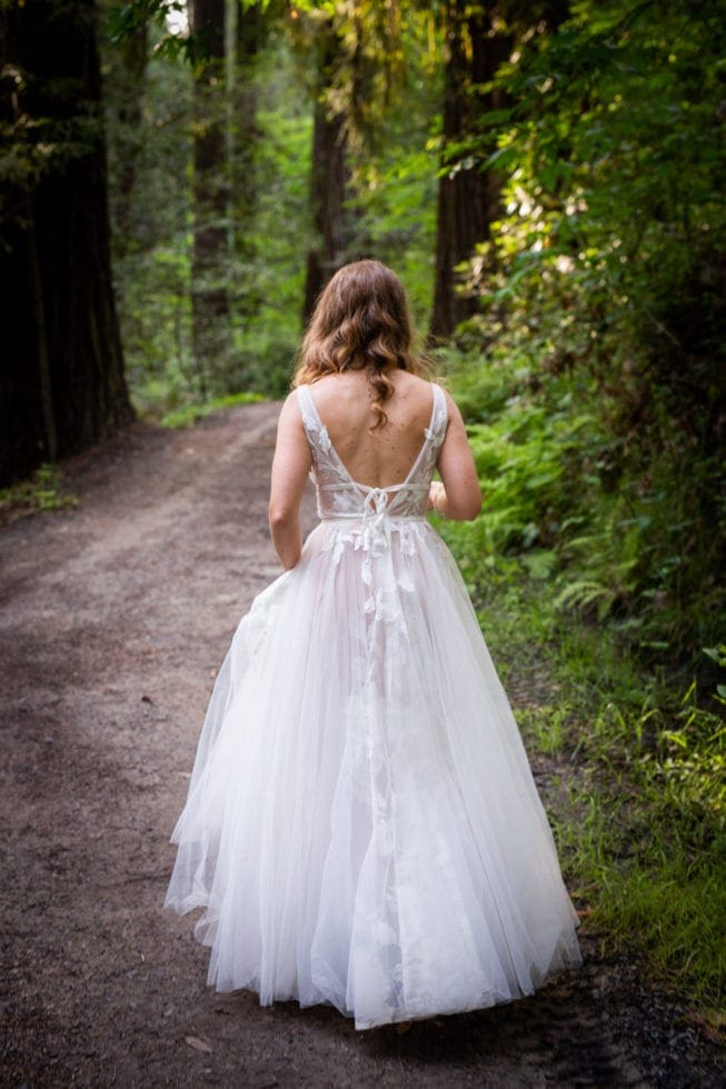 bride walks away from camera on path in griffith woods