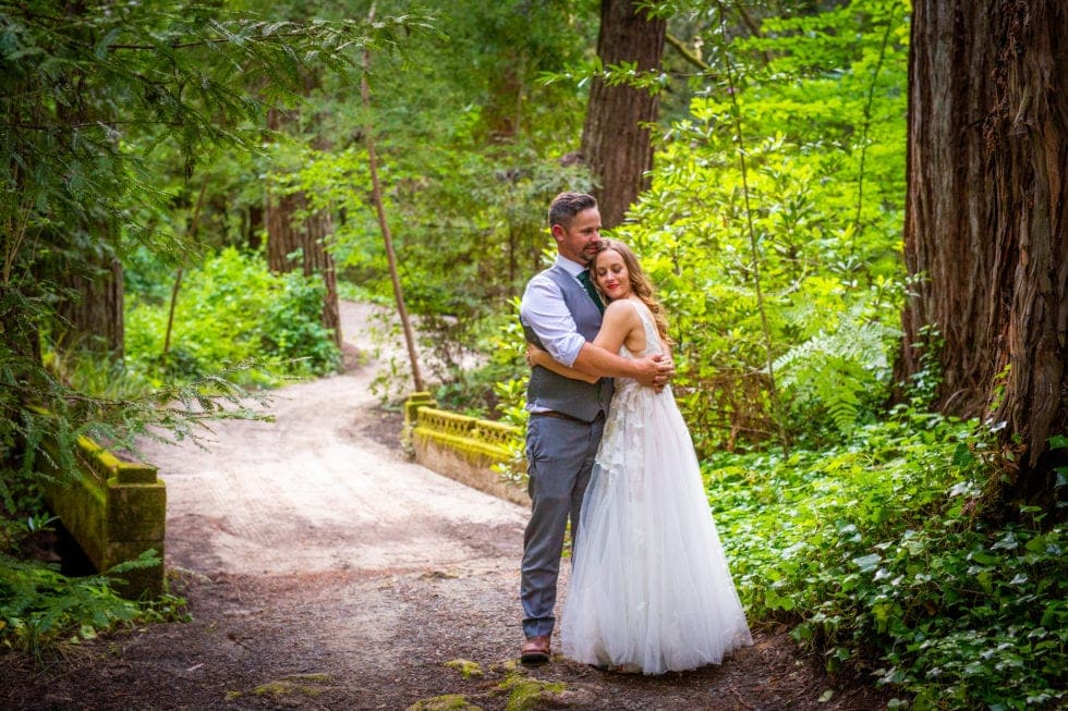 bride and groom embrace on trail in griffith woods