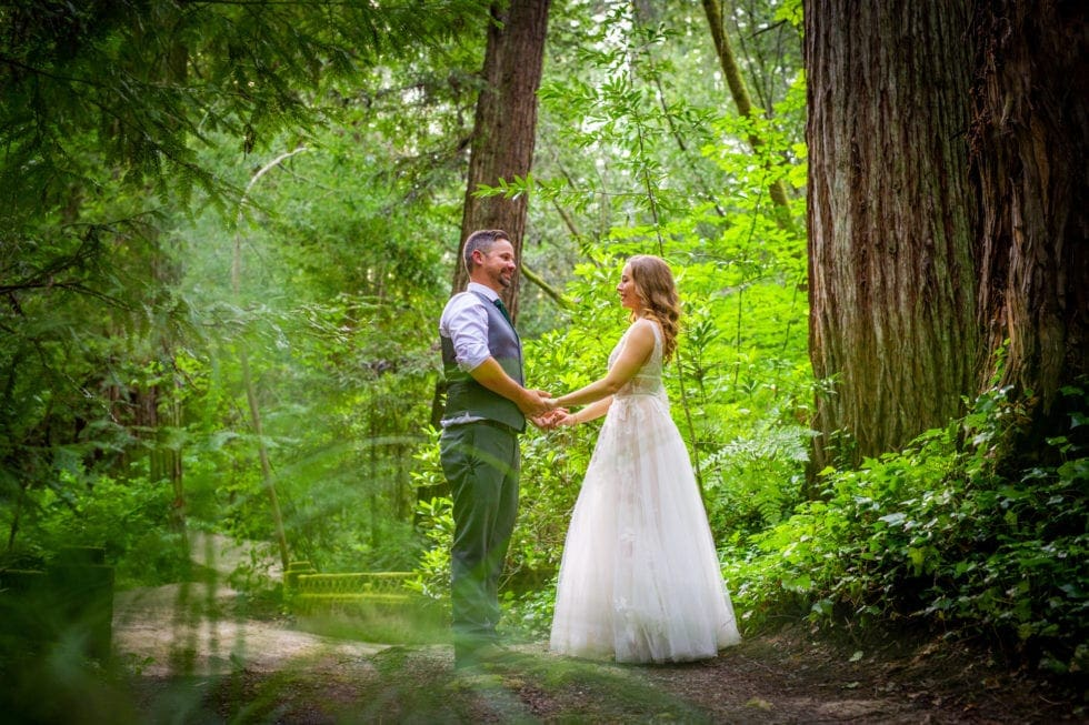 bride and groom holding hands and looking at each other on trail in griffith woods
