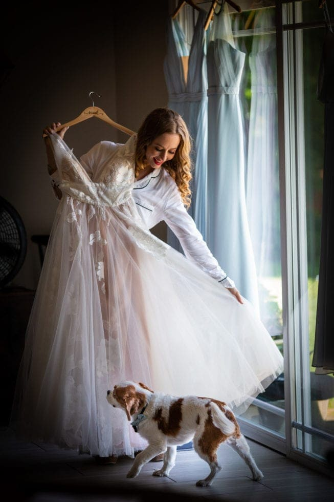 bride holds up her wedding dress while her dog walks by