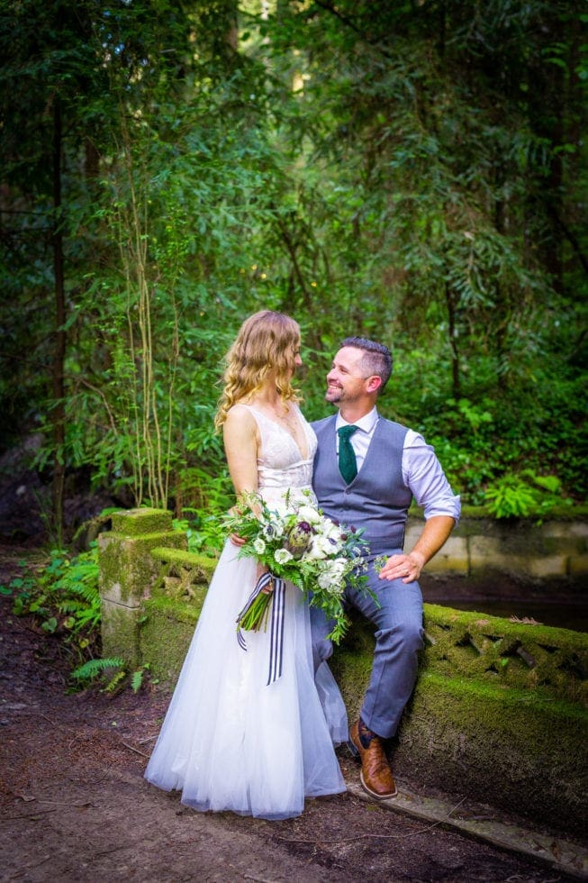 groom sits on wall while bride stands next to him in griffith woods
