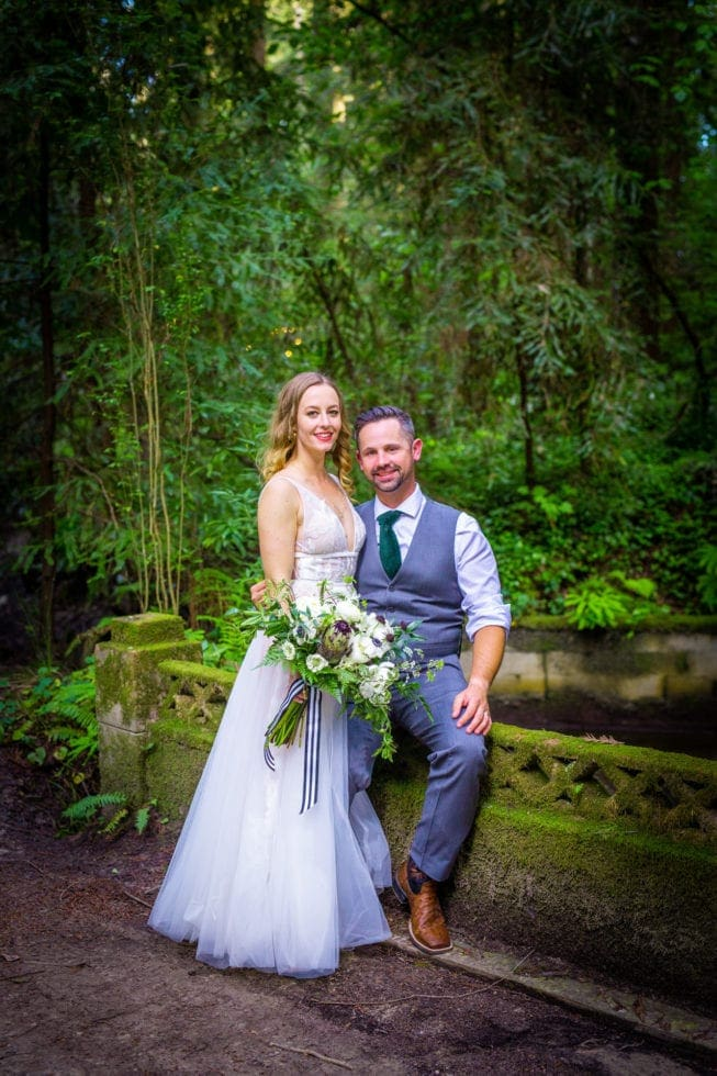 bride and groom smiling at the camera in griffith woods