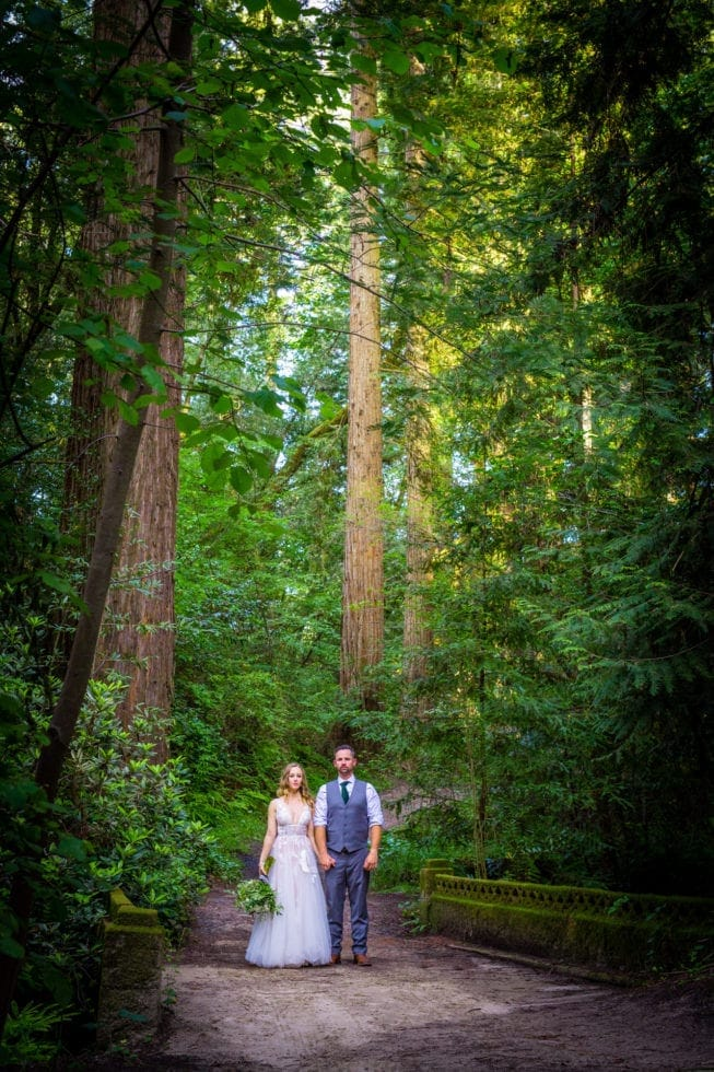 bride and groom standing on path and looking stoic at griffith woods