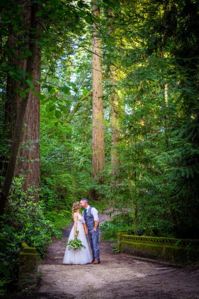 bride and groom kiss on pathway in griffith woods