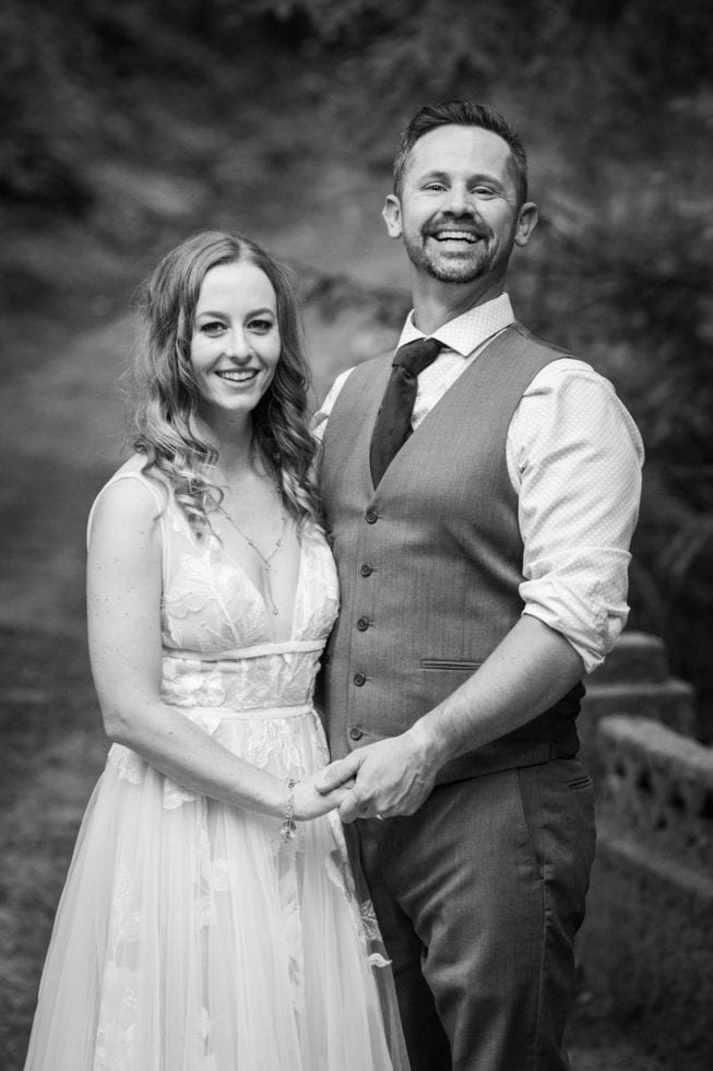 black and white photo of bride and groom smiling at the camera