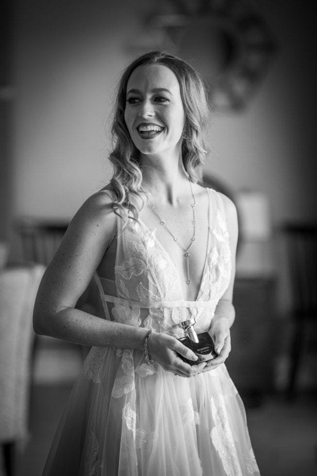 bride smiling and holding a bottle of perfume
