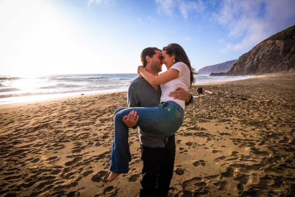 man holding fiance while they smile at each other at point reyes seashore