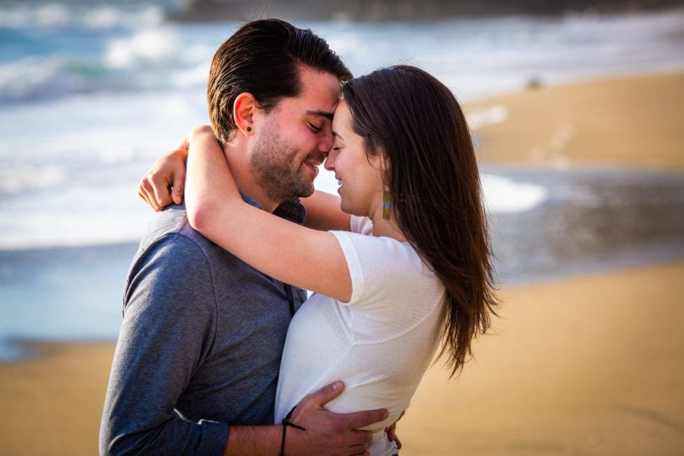 couple embracing with their eyes closed at point reyes seashore