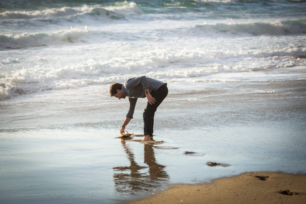 man picking up crab out of the water