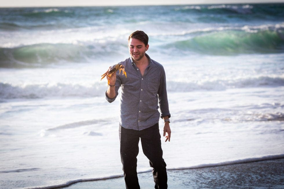 man holding crab in front of the ocean