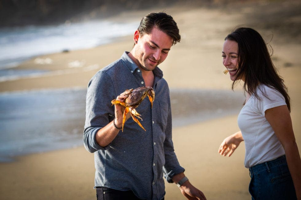 man holding crab while fiance smiles