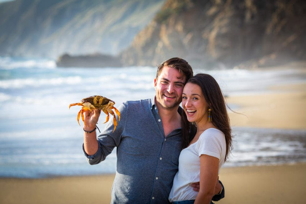 couple smiling while man holds crab