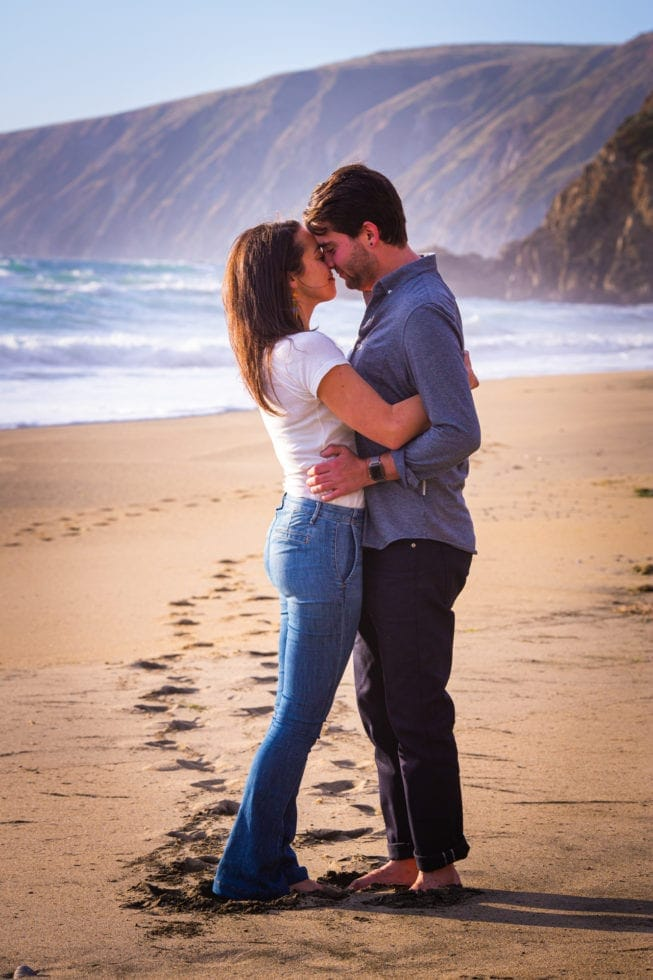 couple embrace in sand with mountains in backgrand at point reyes seashore