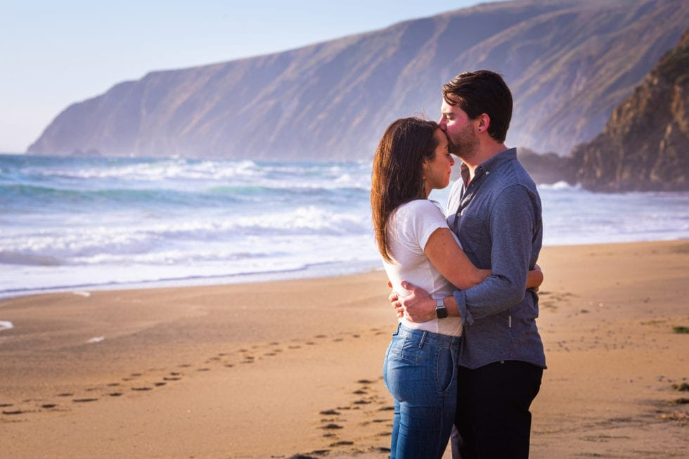 man kisses woman's forehead on the beach at point reyes seashore