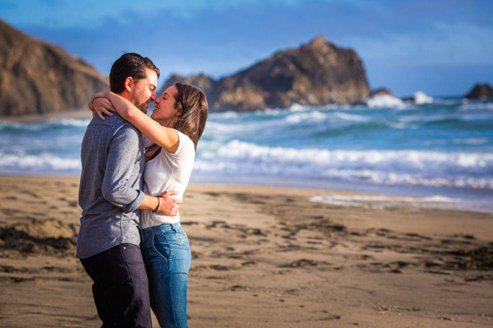 couple embrace in front of beach at point reyes seashore