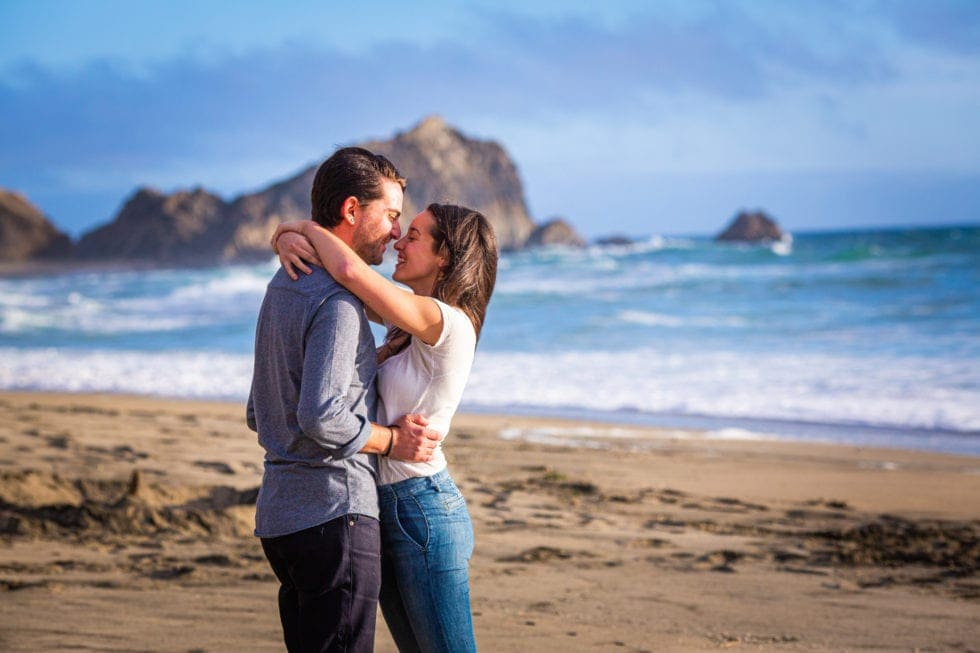 couple smile at each other in front of the ocean at point reyes seashore