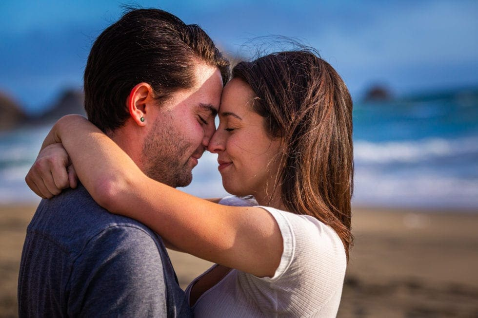 close up of couple embracing with their eyes closed at point reyes seashore