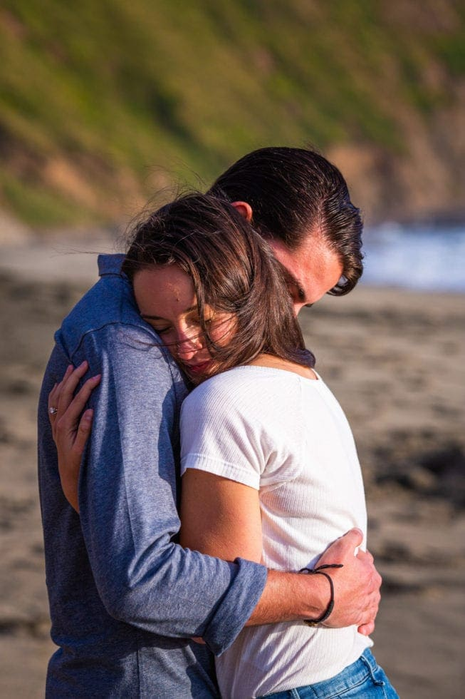 couple embrace during engagement session at point reyes seashore