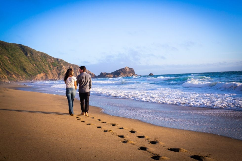 couple walk along the shore for engagement session at point reyes seashore