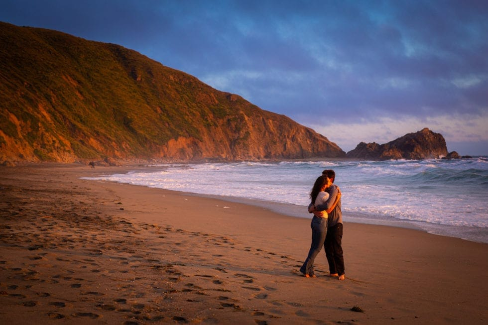 couple embrace on sandy beach at point reyes seashore