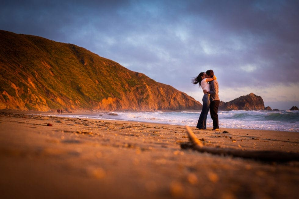 couple kissing on sandy beach at point reyes seashore