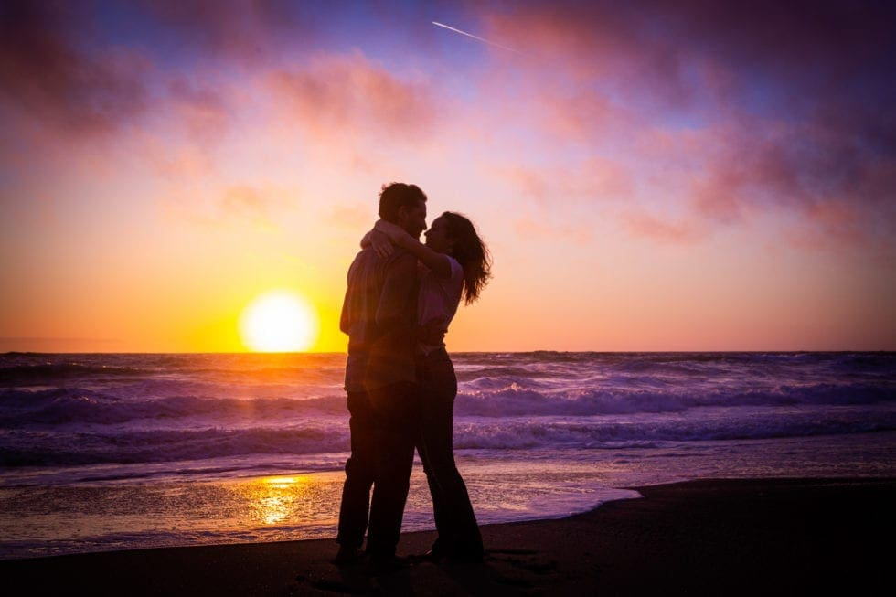 couple standing in front of setting sun at point reyes seashore
