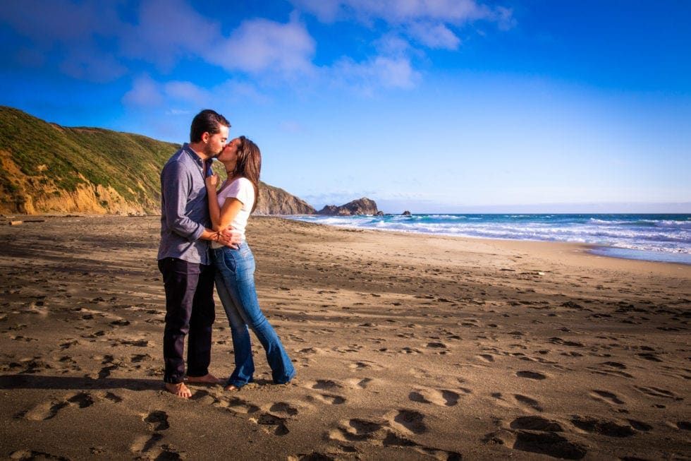 couple kissing at point reyes seashore with hills in background